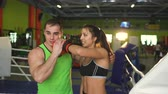 gym : Young woman boxerand her trainer smiling and have fun in boxing ring