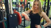front : Strong athletic blonde woman smiling and looking into camera in fitness club Stock Footage