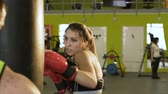 удар : Slow motion of young woman boxer hit punching bag during pre-match warm-up with her trainer