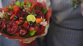 цвести : Woman rotating bouquet of fruits: lime, strawberry, pomegranate, marshmallow, apple