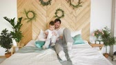 mentira : Happy handsome young father lying on bed and playing with his son