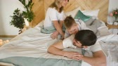 acordo : A young family with little son play on bed in the bedroom