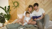 ворсование : loving family of three lying on bed in morning. Family hugging and reading book
