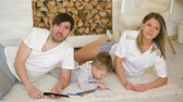 control : Father man mother watch TV while their son draw picture in their living room