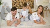 três : Father man mother watch TV while their son draw picture in their living room