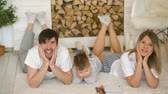 três : Portrait of a lovely family posing and smiling on floor in their living room