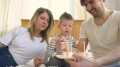подарок : Smiling family celebrating their son birthday together before blowing candles on cake