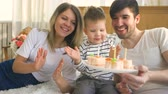 wish : Smiling family celebrating their son birthday together and blowing candles on cake Stock Footage