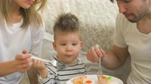 baked : Little adorable boy celebrating his birthday with father and mother eat cake in bedroom