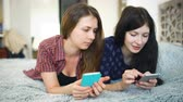 розовый : Two happy women friends sharing social media in a smart phone and talking Стоковые видеозаписи