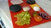 sanduíche : Closeup of chef preparing ingredients for burger grill with vegetables and sauce on kitchen board Vídeos