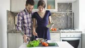 repolho : Happy couple cooking on the kitchen while man kiss her girlfriend at home Vídeos
