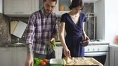 огурцы : Happy young couple cooking in modern kitchen at home