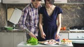 огурцы : Happy couple cooking on the kitchen while man kiss her girlfriend at home Стоковые видеозаписи