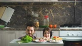 piada : beautiful smiling couple play and kiss above the table with vegetables while cooking in kitchen