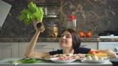 piada : beautiful smiling woman cook play with vegetables on table in kitchen at home Stock Footage