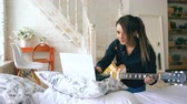 фокус : Attractive young girl learning to play electric guitar with notebook sit on bed in bedroom at home Стоковые видеозаписи