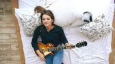 guitarrista : Attractive young girl learning to play electric guitar lie on bed in bedroom at home indoors