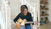 acústico : Attractive young girl learning to play electric guitar sit on stairs in bedroom at home