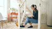 sala : Beautiful woman with headphones and laptop posing and smiling while sitting on stairs at home Vídeos