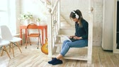 ouvir : Beautiful woman with headphones relaxing with laptop while sitting on stairs in living room at home