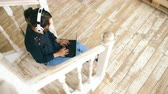sala : Beautiful woman with headphones relaxing with laptop while sitting on stairs in living room at home