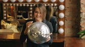 legal : Slow motion of beautiful young woman with disco ball posing and smiling in studio indoors