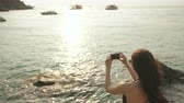 wyspa : Woman tourist on beach island taking photograph of sunset with smartphone on holiday of boat and skyline view