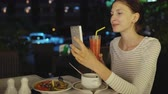 mensagem : Happy woman shoot selfie using smartphone and drinck cocktail juice sitting in restaurant at night
