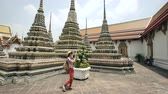 многоцветный : Young woman tourist taking pictures with smartphone at temple sightseeing in Bagnkok Thailand during traveling