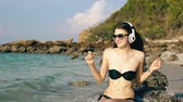 звук : Slow motion of happy beautiful woman listening to music on wireless headphones and dancing at ocean beach