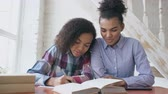 focalizada : Teenage curly haired mixed race young girl sitting at the table concentrating focused learning lessons and her elder sister helps her studying