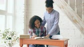 concentrando : Teenage curly haired mixed race young girl sitting at the table concentrating focused learning lessons and her elder sister helps her studying