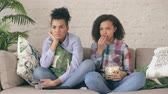 aterrorizada : Two mixed race curly girl friends sitting on the couch and watch nervous TV show and eat popcorn at home Vídeos