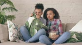 pipoca : Two mixed race curly girl friends sitting on the couch and watch very scary movie on TV and eat popcorn at home