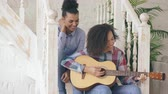 acústico : Two brazilian curly girls sistres sitting on stairs and practice to play acoustic guitar. Friends have fun and singing at home