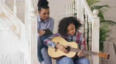 acústico : Mixed race young woman sitting on stairs teaching her teenage sister to play acoustic guitar at home Vídeos