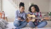acústico : Mixed race young woman with tablet computer sitting on bed teaching her teenage sister to play acoustic guitar at home Vídeos