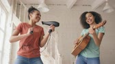acústico : Mixed race young funny girls dance singing with hairdryer and playing acoustic guitar on a bed. Sisters having fun leisure in bedroom at home