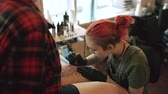 pistola : Red haired girl tattoo artist tattooing picture on lef of young girl client in studio Vídeos