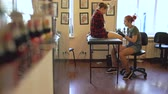 perna : Beautiful red haired woman tattoo artist tattooing picture on leg of young girl client in studio