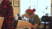 mürekkep : Young female red haired tattoo artist tattooing picture on leg of client over sketch in studio indoors