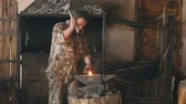 fogo : Slowmotion of bearded young man blacksmith manually forging hot metal on the anvil in smithy with spark fireworks Vídeos