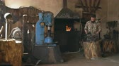 craft : Young man blacksmith manually forging hot metal knife on anvil in traditional smithy Stock Footage