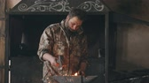 fajerwerki : Slowmotion of bearded young man blacksmith manually forging hot metal on the anvil in smithy with spark fireworks Wideo