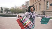 outono : Attractive mixed race girl dancing and have fun while walking down the street with bags. Happy young woman walking after shopping on mall sale