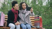 distância : Two cheerful african american women with shopping bags having video call with tablet computer. Young friends sitting on bench have online chat Vídeos