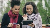 paper : Two attractive mixed race women with paper bags sitting on bench and using tablet computer and credit card for online shopping