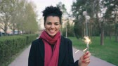 fajerwerki : Attractive mixed race young woman lights a sparkler firework and smiling in park