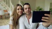 closeness : Young cute and loving couple having video chat holding tablet computer and chatting to friends sitting in bed at home